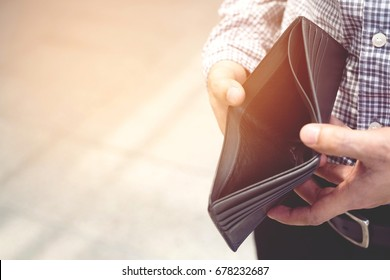 Empty wallet (no money) in the hands of an man. Cost control expenses poverty   in concept