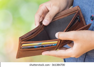 empty wallet (no money) in man hand over blurred green background