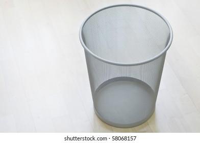 An empty waste-bin on wooden floor