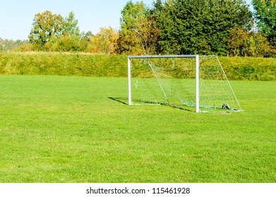 Empty and well used soccer goal on open grass field.