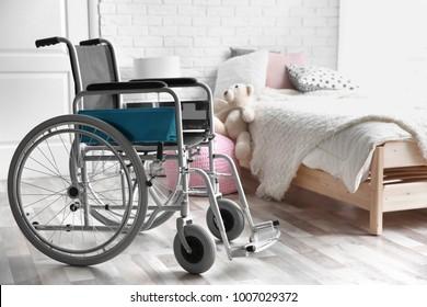 Empty wheelchair in children's bedroom