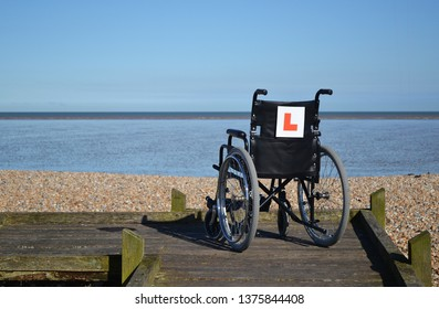 Empty wheelchair facing seafront on ramp with an 'L plate' on back of chair