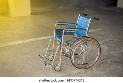Empty wheelchair on the cement floor in hospital, Wheelchair for patients with dark background, health care and Insurance concept.