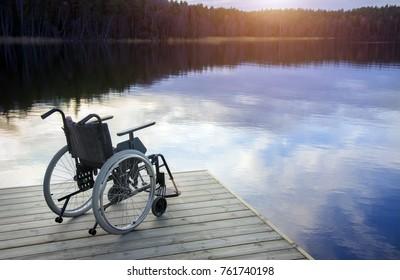 Empty wheelchair  on wooden bridge at dusk