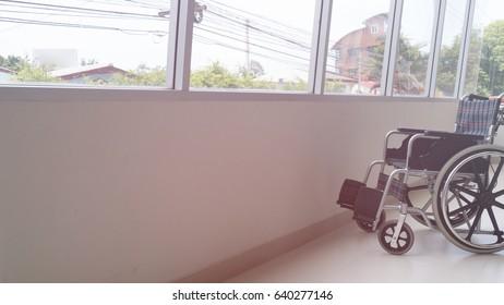 Empty wheelchair parked in hospital hallway beside window