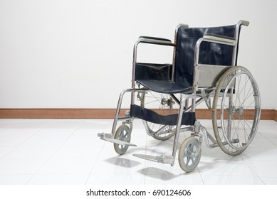 Empty wheelchair parked in hospital on white wall background, A wheelchair for the sick or disabled is placed on the red carpet. The back wall is white.