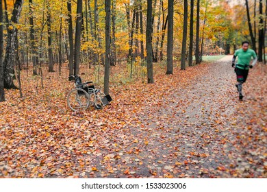 Empty wheelchair and running athlete runner in the autumn forest, concept of hope and miracle, mobility and recovery of disabled people. Active and healthy lifestyle.