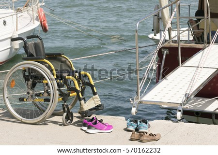 77f6c26ee Empty wheelchair and shoes on the beach near the sea with boats