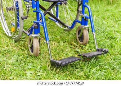 Empty wheelchair standing on grass in hospital park waiting for patient services. Invalid chair for disabled people parked outdoor in nature. Handicap accessible symbol. Health care medical concept