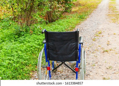 Empty wheelchair standing on road in hospital park waiting for patient services. Invalid chair for disabled people parked outdoor in nature. Handicap accessible symbol. Health care medical concept