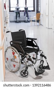 An empty wheelchair stands in front of two bicycle training devices with patients.