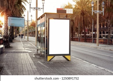 Empty white advertising urban billboard near city bus stop, placeholder template on a street, space for design layout. sunset