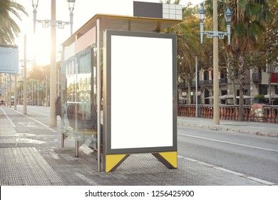 Empty white advertising urban billboard near city bus stop, placeholder template on a street, space for design layout.
