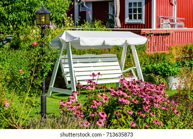 Empty white canopy swing or patio swing in green flower garden. Lamppost and flowers in foreground and red cabin in background.