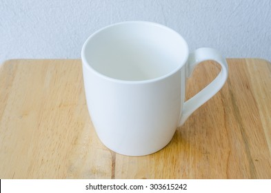 Empty white ceramic cup on wooden table.