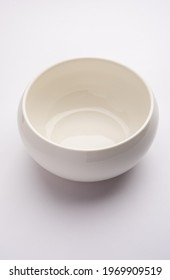 Empty white ceramic serving bowl, isolated over white or gray background