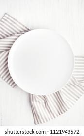 Plaque de cercle blanc vide sur table en bois avec serviette en lin.  Vue de dessus.