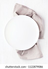 Empty white circle plate on wooden table with linen napkin. Overhead view, mock up.