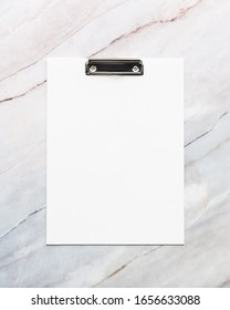 empty white clipboard on marble table background. template for text, mockup, copy space. vertical orientation