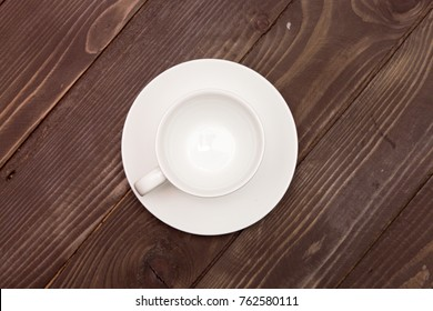 Empty white Cup with saucer on a wooden background, top view . Crockery for coffee and tea , chocolate, espresso.