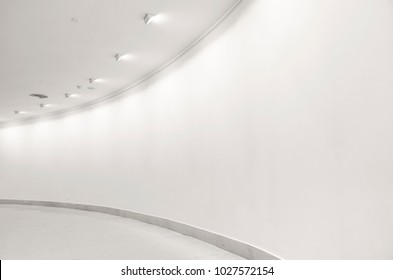 Empty white curved corridor with studio spotlight shining on the wall