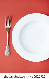 An empty white dinner plate and fork on a red background