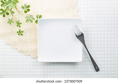 An empty white dinner plate with silver fork on a white mosaic tile background