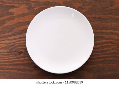 empty white dish on the brown table