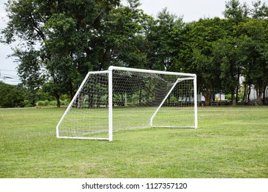 Empty white football, soccer goal with net on the football grass fields in school with tree background