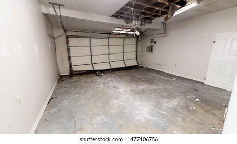 An empty white garage with a sagging ceiling