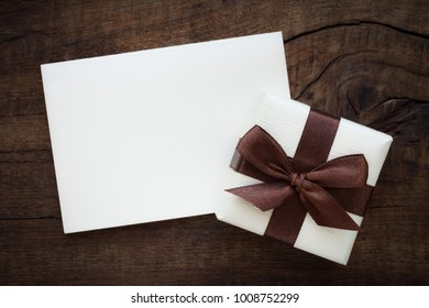 Empty white greeting card with a beautifut gift box with a brown bow on dark rustic wooden background