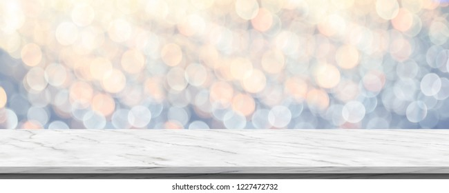 Empty white marble glossy table top with blur sparkling soft pastel blue and orange bokeh abstract background,panoramic banner for display or montage of product,Holiday seasonal concept backdrop