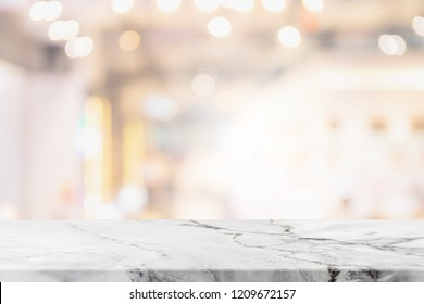 Empty white marble stone table top on blurred with bokeh shopping mall interior background - can be used for display or montage your products