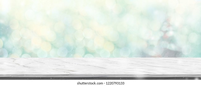 Empty white marble table with abstract blur green christmas tree and snow fall background with bokeh light.Mock up banner for display of product