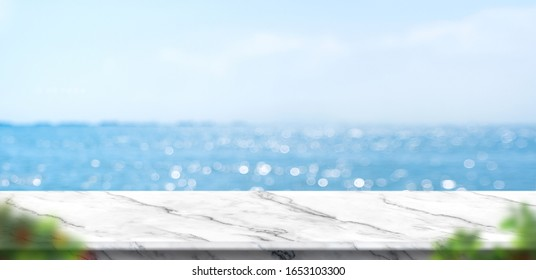 Empty white marble table with blur blue sky and sea bokeh background with green leaf foreground,Mock up template for display or montage of product or content use as banner in social media ads