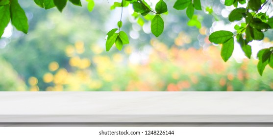 Empty white marble table over blur green nature park background, product display montage