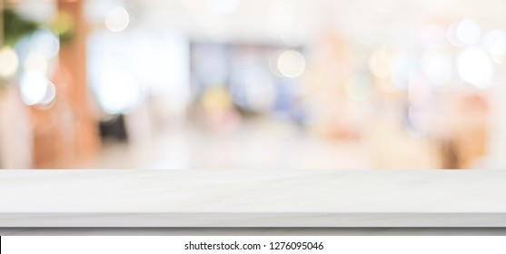 Empty white marble table over blur store background, banner, product display montage