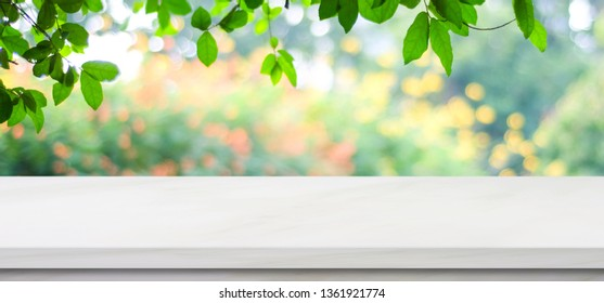 Empty white marble table over blur green tree nature park background, product display montage