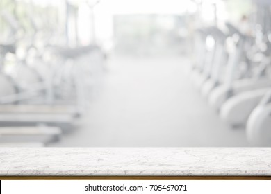 Empty white marble table space platform and fitness gym background. Product display montage Concept.