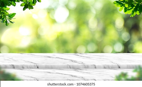 Empty white marble table top with blur tree in park with bokeh light at background,Mock up template for display of your design,Banner for advertise of product,panorama view.