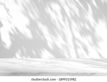 Empty white marble tabletop with shadow of leaves on concrete wall background.