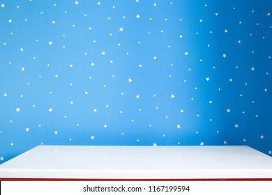 empty white night table and blue starry wall in nursery