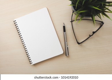 Empty white notebook top view on wood table close to pen and glasses