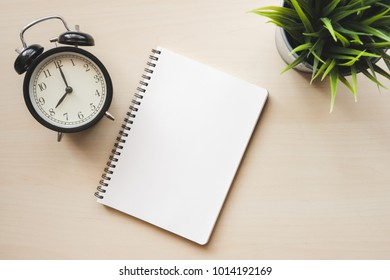 Empty white notebook top view with black alarm clock on wooden table