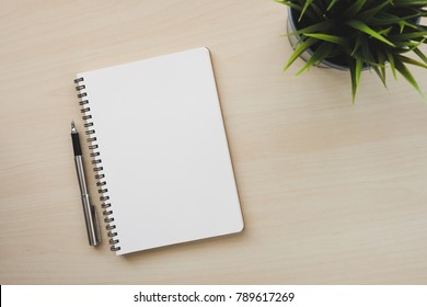 Empty white notebook top view with pen on wooden table