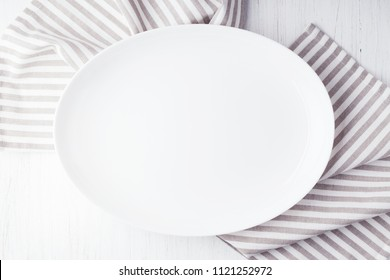 Empty white oval plate on wooden table with striped linen napkin. Overhead view.