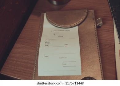 ฺBrown empty white paper in restaurant payment billing receipt folder on granite table