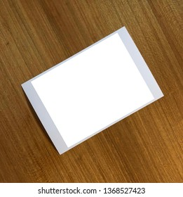 Empty white Photograph over wood table.