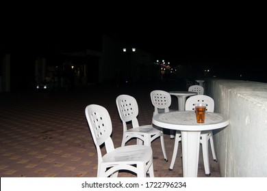 An empty white plastic summer table on the summer promenade, around a few chairs. Lunch party. A lonely glass with a drink on the table. Everyone gone.