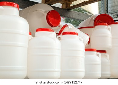 Empty white plastic water-cans with red lids on a rack. Domestic drinking water tanks.
